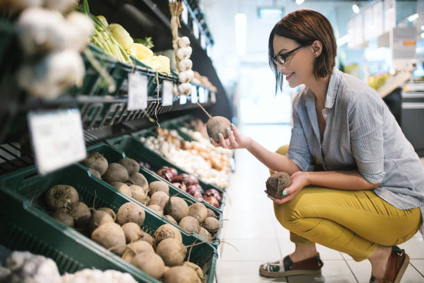 Buying fresh beet. Attractive brunette woman choosing lettuce to buy in a supermarket. produce aisle stock pictures, royalty-free photos & images