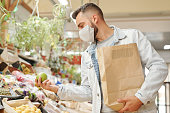 Young man in facial mask holding paper bag and choosing fruits while buying fresh groceries at organic market