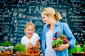 A mother and daughter are at a farmer's market together. They are carrying baskets of vegetables including: carrots, tomatoes, and beets. They are smiling while in front of a large blackboard.