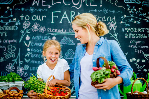 Buying From The Market A mother and daughter are at a farmer's market together. They are carrying baskets of vegetables including: carrots, tomatoes, and beets. They are smiling while in front of a large blackboard. farmer's market stock pictures, royalty-free photos & images