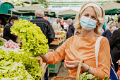 Senior woman wearing a protective mask while buying groceries at the market