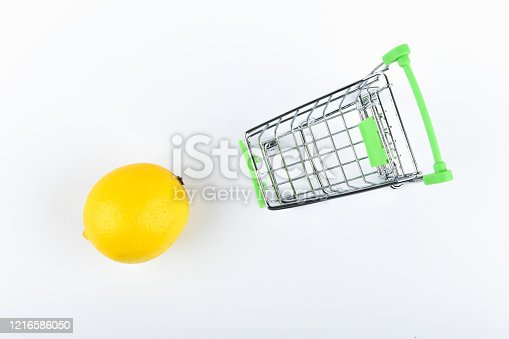 511190632 istock photo buying lemons. trading concept. Online shopping concept. Cart and lemons over a white background. business concept. Healthy eating concept 1216586050