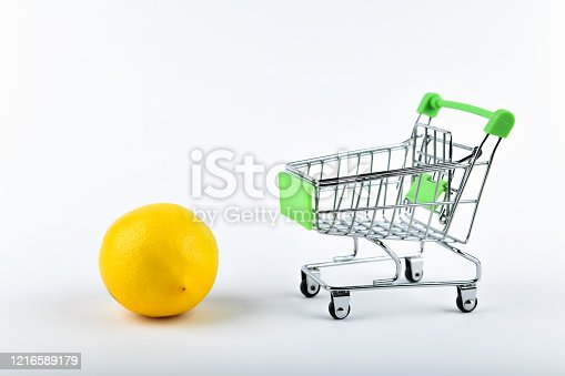 511190632 istock photo buying lemons. trading concept. Online shopping concept. Cart and lemons over a white background. business concept. Healthy eating concept 1216589179