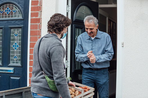 Man delivering fruit and vegetables to a front door where a senior man collects them, paying for them. They are sustainably grown in the North East of England.