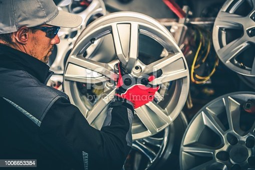 Buying New Alloy Wheels and Seasonal Tires Change Concept Photo. Caucasian Car Service Worker with Large Rim in Hands.