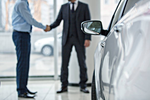 Buying new car at car showroom Handshake between two business people in a car showroom. car salesperson stock pictures, royalty-free photos & images