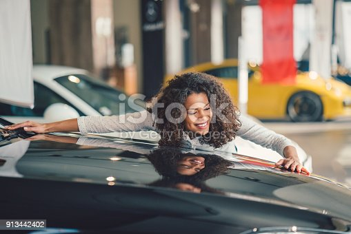 Young woman in love with her new car