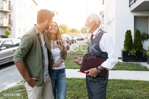 Young couple talking with real estate agent and buying a new house.