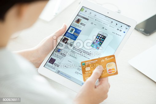 Kiev, Ukraine - June 27, 2014: Person holding a credit card and trying to buy a new Apple iPhone 5 with eBay application on a brand new Apple iPad Air. eBay is the worldwide online auction and shopping website, founded in September 3, 1995.