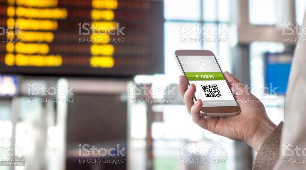 Buying online ticket from internet. E-ticket on mobile phone screen with schedule in the blurred background. Universal public transportation terminal. Bus, train, metro, subway or underground station stock photo