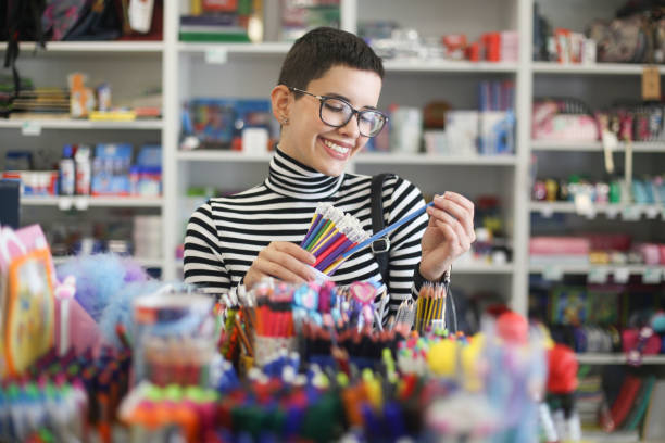 Buying school supplies Young woman shopping for school supplies in a stationery store. About 20 years old, Caucasian brunette with short hair. office equipment stock pictures, royalty-free photos & images