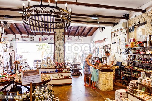 Mother and daughter are buying souvenirs in the Greek gift shop. Real people, authentic scene.