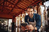 Shot of a cheerful young barman browsing on a digital tablet while patiently waiting at the bar for customers inside of a beer brewery during the day