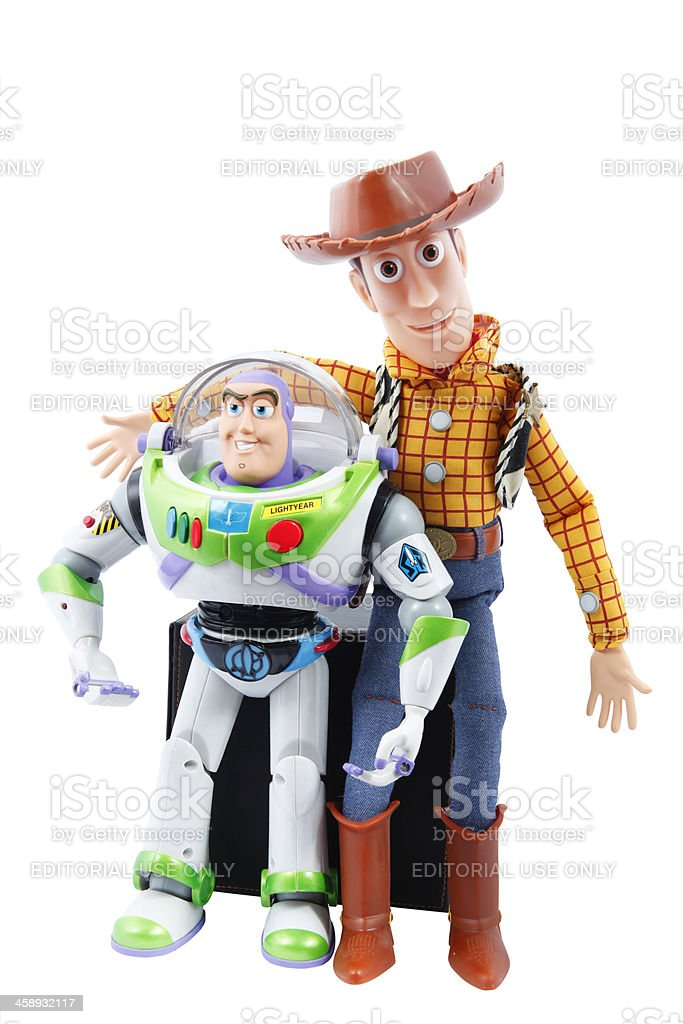 Buzz Lightyear and Woody Cantley, Canada - September 21, 2012: You can see Talking Buzz Lightyear Space Ranger toy and talking Woody cowboy doll. Those two characters are from Pixar Disney movies: Toy Story, Toy Story 2 and Toy Story 3. The two toys are leaning against a black block. All is on a white background. Arts Culture and Entertainment Stock Photo