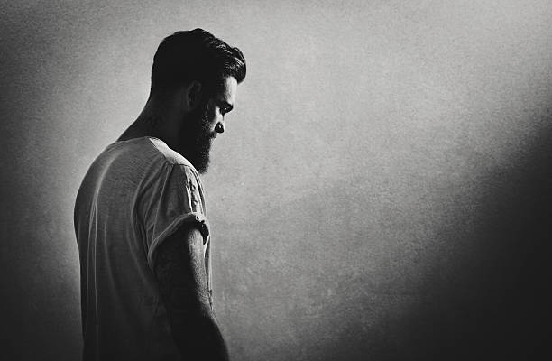 B/w portrait of a bearded tattooed guy stock photo