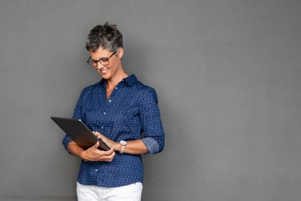 bwauriful smature business woman using tablet - senior business woman tablet imagens e fotografias de stock