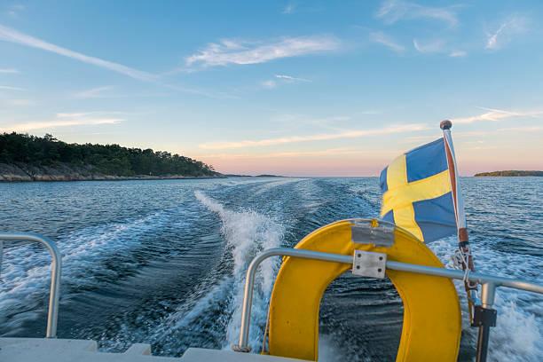 De barco ao pôr-do-sol, arquipélago de Estocolmo, na Suécia. - foto de acervo