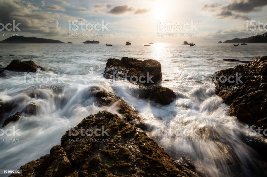 By the sea during the time of sunset with rock and the crashing waves. Beautiful natural summer seascape royalty-free stock photo