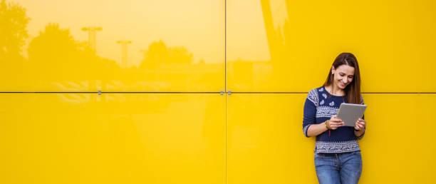 by the yellow wall - online shopping imagens e fotografias de stock