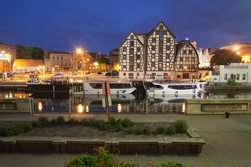 City of Bydgoszcz at night in Poland, Granaries, tour boats and waterfront along Brda River.
