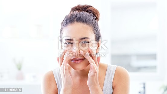 Cropped shot of a beautiful young woman squeezing a pimple in the mirror