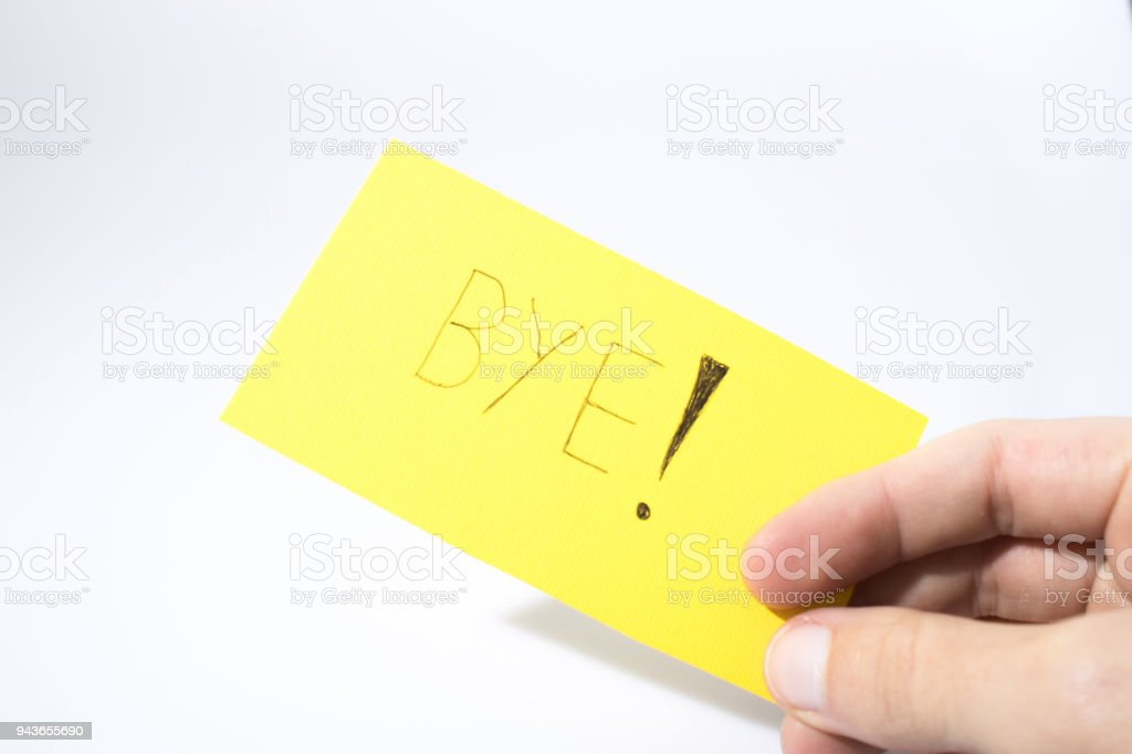 Bye handwrite with a hand on a yellow paper composition stock photo