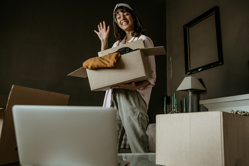 Women, owner of small business packing product in boxes, preparing them for delivery and waving to a camera during a video call.