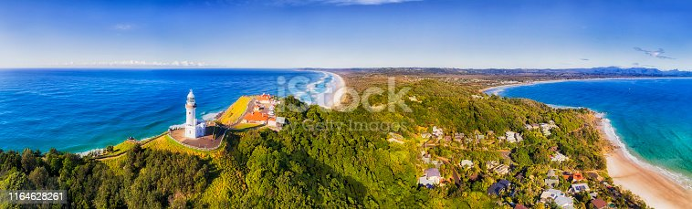 Top of headland with Byron Bay lighthouse high above Pacific ocean coast on a sunny day in elevated aerial panorama facing inland over sandy beaches.