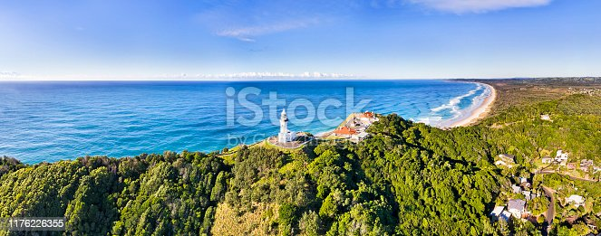Sandstone headland hill range at the tip near Byron Bay town with wHite stone Byron Bay lighthouse on the top in wide aerial panorama overlooking Pacific ocean and coast with beaches under blue sky.