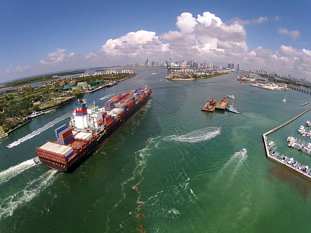 Caargo ship enters port aerial view Heavy cargo ship enters the port of Miami aerial view canal stock pictures, royalty-free photos & images
