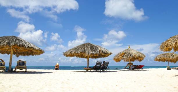 Cabana, parasol. Plage de sable blanc. Eau de mer bleue et nuages dramatiques. Oranjestad, Aruba. Célèbre Eagle Beach.  Baigneur de soleil non identifiable. - Photo