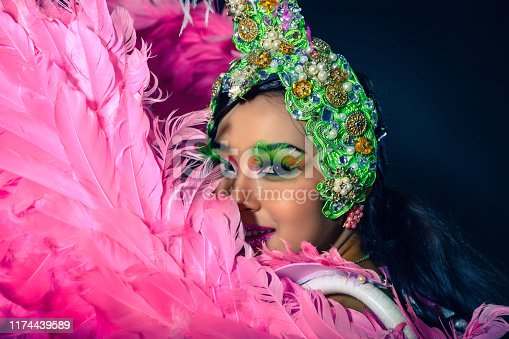 Show beautiful woman with fantasy dress and head gear for performance on background