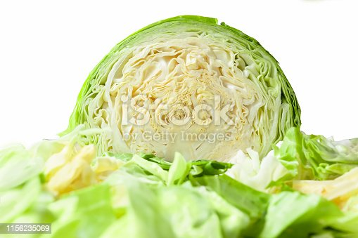 Cabbage head cut in half, isolated on a white background, with shredded cabbage leaves in foreground