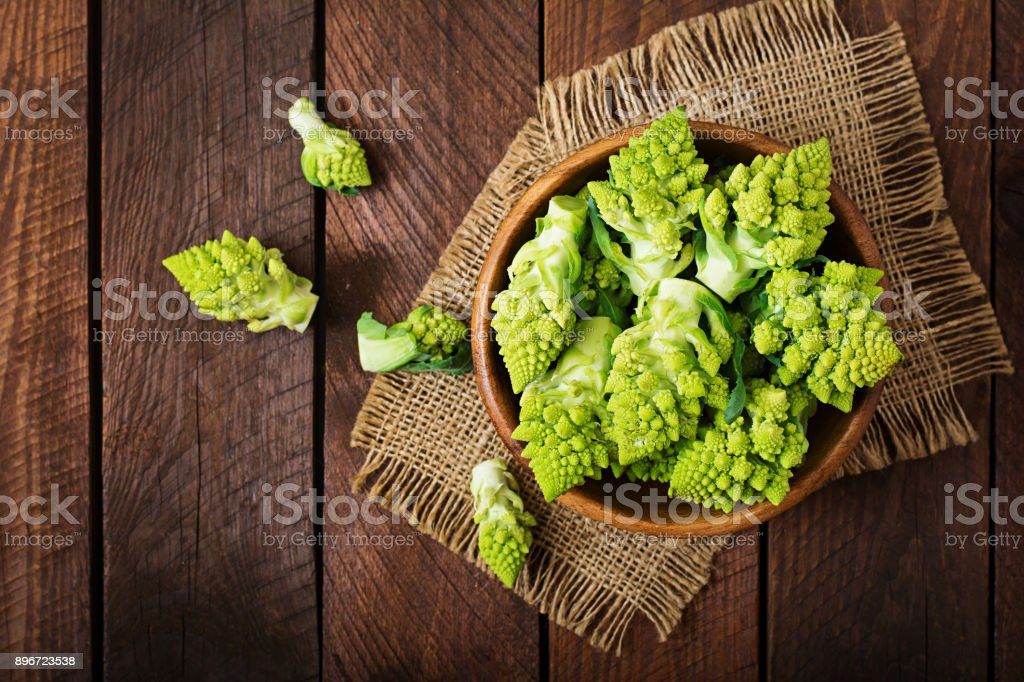 Cabbage romanesco on a dark wooden background. Top view stock photo