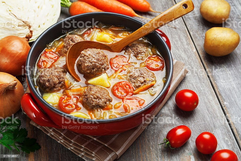 Cabbage soup with meatballs and tomatoes stock photo