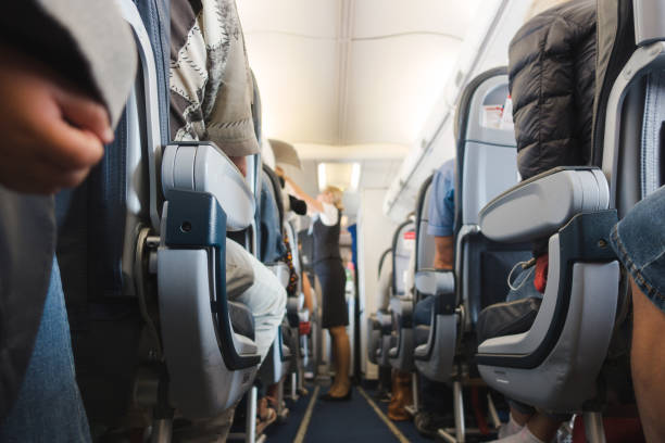 Cabin aisle in airplane Cabin aisle in airplane with rows of seats and passengers. cabin crew stock pictures, royalty-free photos & images