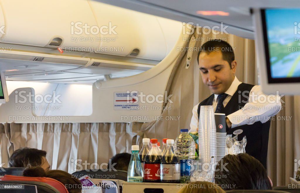 Cabin crew member serving breakfast. stock photo