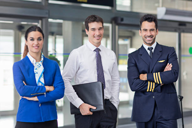 Cabin crew members with pilot standing at airport stock photo