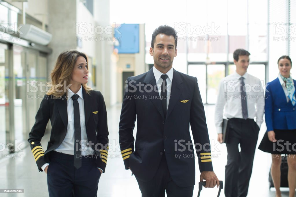Cabin crew walking through the airport. stock photo