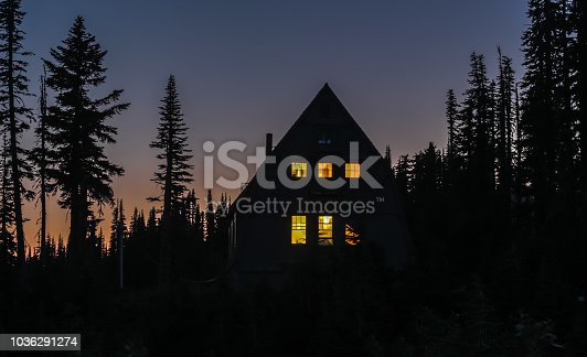 Wooden cabin in the woods at night; windows are lit