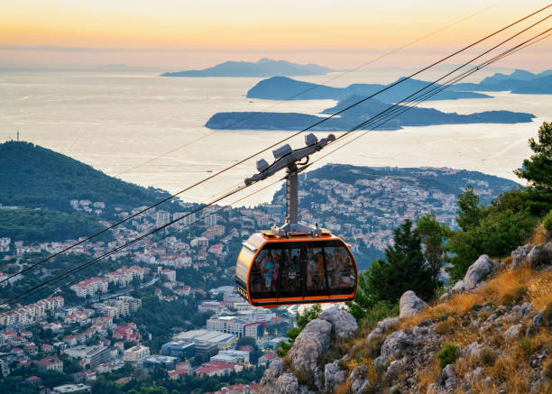 Cabin of cableway and ancient Dubrovnik at sunset Dubrovnik, Croatia - August 20, 2016: Cabin of cableway and ancient Dubrovnik at sunset, Croatia croatian culture stock pictures, royalty-free photos & images
