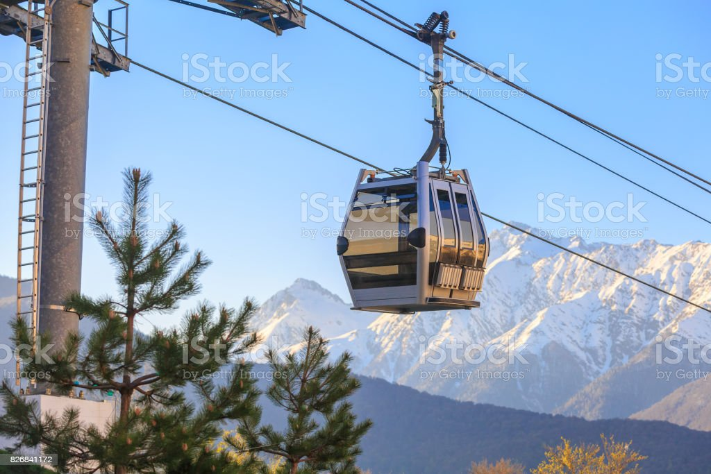 Cabin of funicular on the background of snow-capped mountains at sunset stock photo