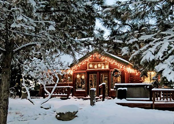 cabin with christmas lights - kütük ev stok fotoğraflar ve resimler