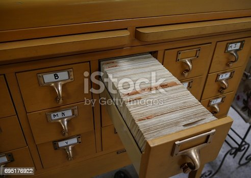 A sturdy wooden cabinet containing index cards of a library cataloguing system