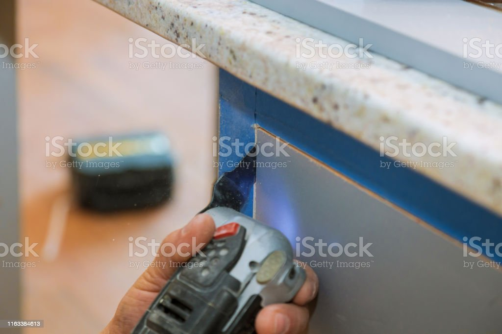 Cabinet Furniture Cutting Oscillating Multifunction Power Tool On Kitchen Cabinets Framing Stock Photo Download Image Now Istock