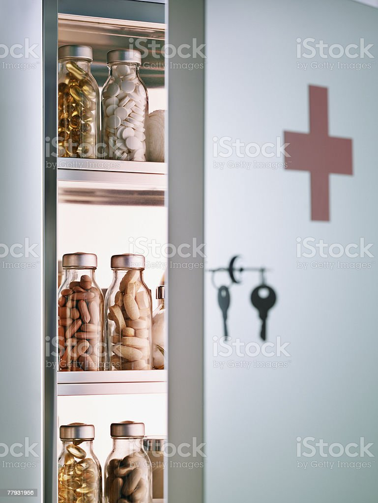 Cabinet with pill bottles next to hanging keys  stock photo