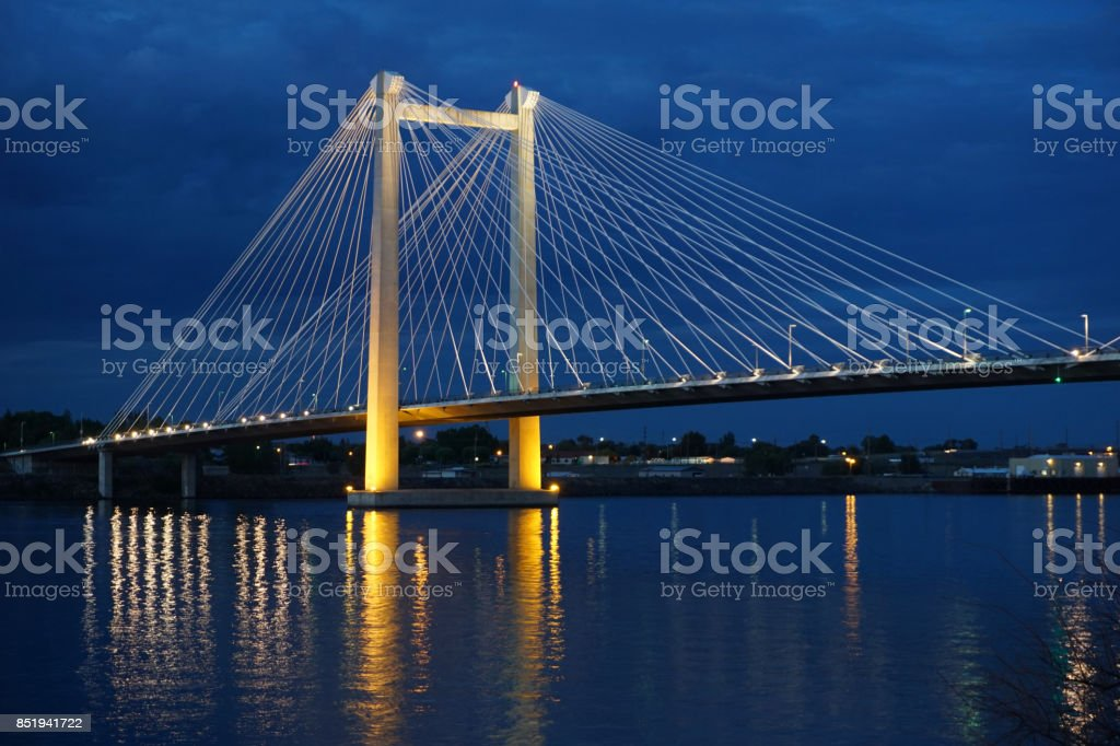 cable bridge lit up at night stock photo