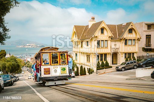 Historic Powell-Hyde cable car climbing up steep hill in central San Francisco with famous Alcatraz Island in the background on a sunny day with blue sky, USA.