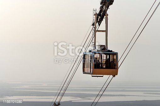 cable car lifts tourists to the mountain fortress of Masada. Funicular on the background of the Judean desert, the dead sea and the cloudy sky. Desert beautiful landscape.
