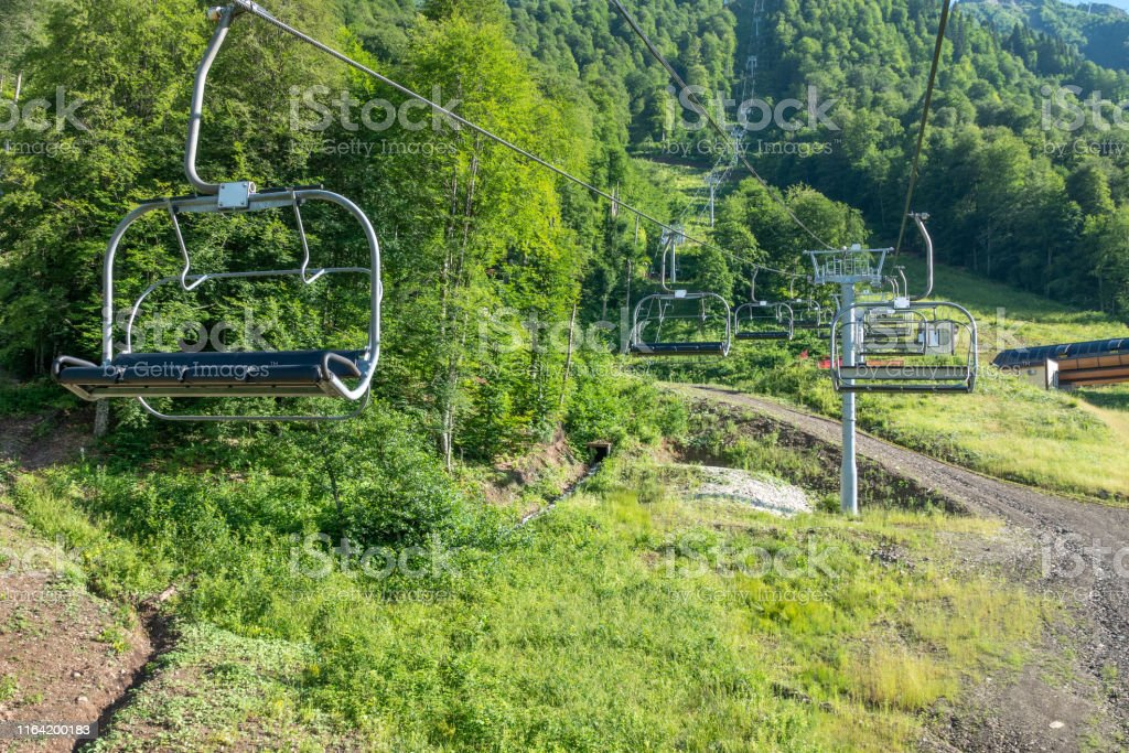Cable car with open chair lifts in summer. Supports and cable car...